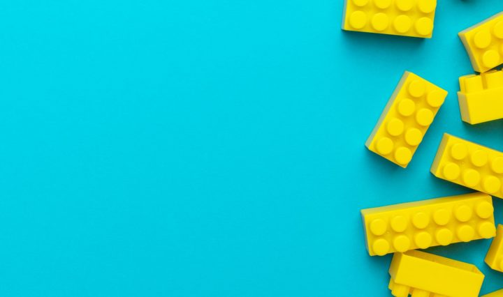 Yellow Plastic Building Blocks On Turquoise Blue Background With Copy Space
